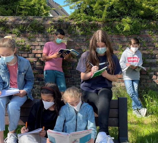 Schüler sitzen auf einer Bank im Sommer und lernen